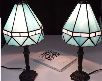 A pair of turquoise blue and white stained glass lampshades with antique bronze lamp bases