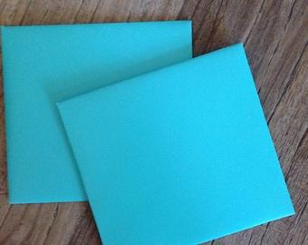 Two square mint-green envelopes