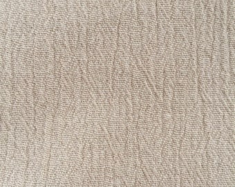 Slightly pleated beige cotton fabric