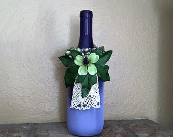 Re-purposed wine bottle vase purple with green flower