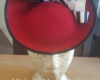 red saucer hat with black and white trim