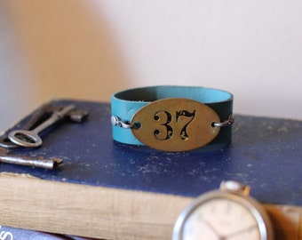 Blue leather cuff, and Vintage brass Room number bracelet