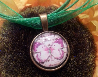 Pink Butterfly cabochon pendant on a  dark green chiffon cord necklace