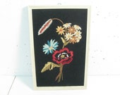 Vintage framed embroidery of flowers on black background