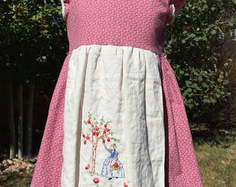 Lady picking apples on dusty rose apron dress