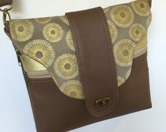 Cross body zipper vegan bag in tan and gold with flap.