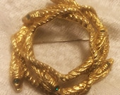 Vintage Intertwined Six Snake Circle Brooch with Green Eyes. It Measures About Two Inches in Diameter. It is in Very Good Condition. (J100)