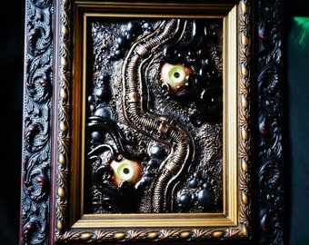 Framed biomech eyes and tentacles sculpture