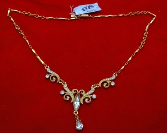 """1928 brand Vintage gold tone 18"""" necklace with attached 3"""" rhinestone pendant in unworn condition, 2"""" center drape"""