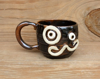 Coffee Cup for Guys. Man's Mustache Mug with Monocle Eyepiece. 12 Ounce Dark Chocolate Brown Black. Funny Nelson Studio Ug Chug Coffee Cups.