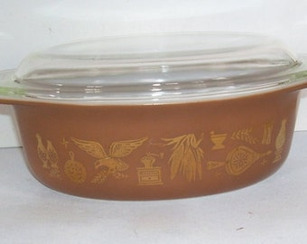 Pyrex 1 1/2 Quart glass serving dish, Early Americana pattern in warm brown with gold American images, Original oval clear glass lid