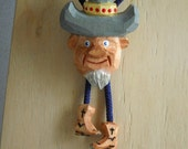Bolo Tie with cowboy caricature and carved boot cord tips