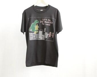 vintage 90s men's shirt DINOSAUR eating SAN FRANCISCO for lunch faded black t shirt