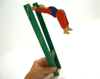 Trapeze artist acrobat wooden string toys, man jumps, 360 degree circular swings between wood poles, red blue green tan, midcentury vintage
