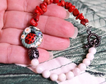 LADY BUG ARTISAN Ceramic Focal Bead Coral and White Shell Bead Gunmetal Toggle Bracelet
