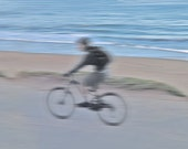 Bicycle rider on beach light pink blue, motion blur California wall decor, minimalist landscape
