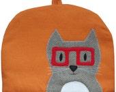 Cat in red glasses, large teapot tea cosy in orange