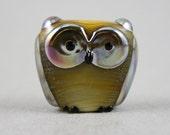 Metallic and ocher-ivory owl bead (Item 151088B)