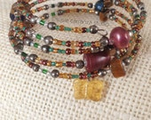 Bohemian Chic Wire Bracelet. Variety of beads: glass, acrylic, metal, stone, iridescent seed beads. Glass butterfly charm.