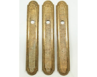 Set of three gilded bronze beaded plates