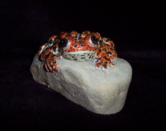 hand sculpted warty toad on a rock
