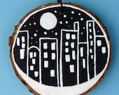 Cityscape on wood tree slice, birch, Christmas ornament, painted, night sky, small round art, black and white, New York City, snow