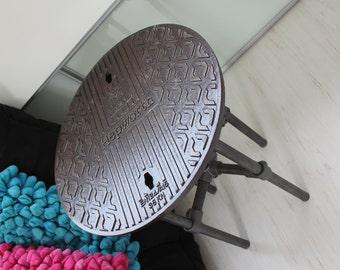 Lefton Reclaimed Manhole Cover Side Table with 4 Cross Braced Dark Steel Legs and Bright Orange Underside - www.inspiritdeco.com