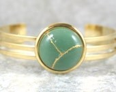 Kintsugi (kintsukuroi) cuff bracelet with green aventurine stone cabochon with gold repair in a gold plated setting - OOAK