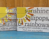 Sunshine, Lollipops, and Rainbows hand painted pallet style sign on fence boards