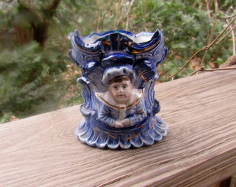 flow blue jar with leaves and small boy