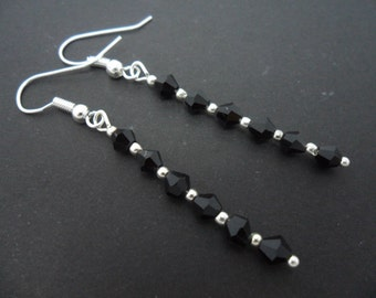 A pair of hand made silver plated black crystal dangly earrings.