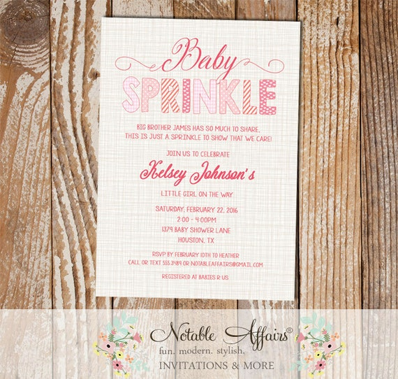 baby girl baby sprinkle invitation on brown linen background pinks
