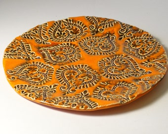 ceramic plate, round, with stamped pattern, orange and brown, textured, decorative plate