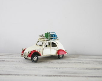 Deux Chevaux car miniature, vintage French white 2CV Citroen collectible miniature with red fenders and baggage on the rack, mid nineties