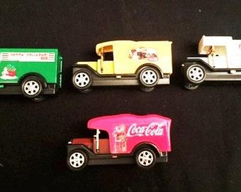 Four plastic Coca Cola delivery trucks