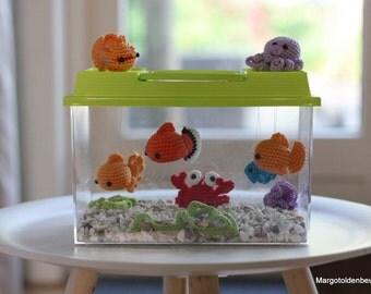 Plastic aquarium with crochet fish, crab and squid