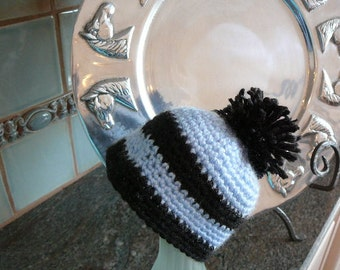 Blue and black hat with black pom pom on top