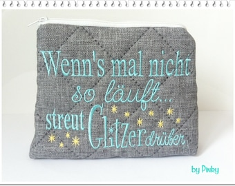 Cosmetics bag spreading glitter over turquoise