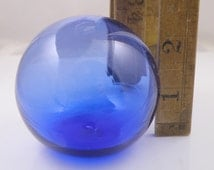 Glass gazing ball. Cobalt blue hollow float. Flat base. Approximately 2.5 inches or 6 cm in diameter. Rich transparent color.