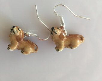 Tiny porcelain Dachschond earrings hanging on sterling french hook earwires.