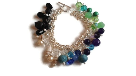 A multi-colored gemstone and crystal charm bracelet in silver.