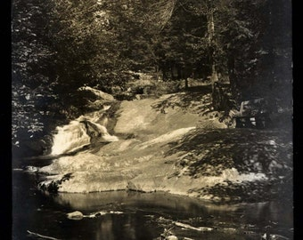 C. 1910 RPPC Photo Postcard. Sunlit view of Bench along River, Forest
