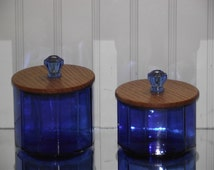 """Two 12 sided cobalt blue canning jars, cut down to size & fitted with  two part cross grained lids and 1"""" light blue fluted glass knobs."""