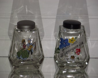 A pair of European made heavy glass bottles, one with a fired on decal and the other is entirely hand painted.
