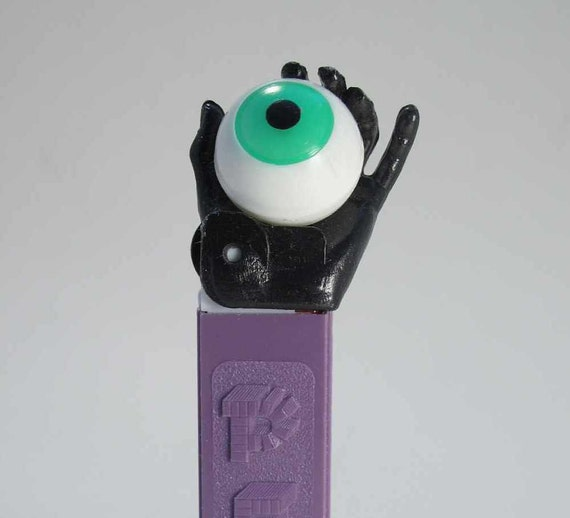Vintage Psychedelic Eye Pez dispenser, black hand, purple stem. Beautiful NEAR MINT, vintage Pez dispenser, made in Austria 26 stem, 60s Pez