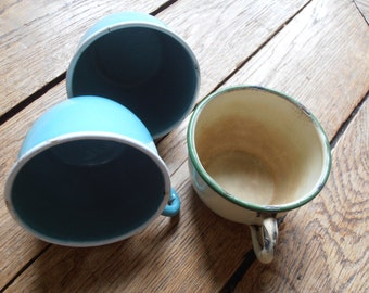 Three vintage enamel cups, one yellow, two robin's egg blue