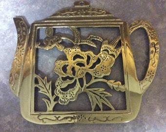A Brass Tea Pot Shape Trivet with a Floral Design, Hampton.