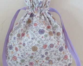 Liberty of London drawstring bag, floral design, lavender, pink, yellow, and green on white background