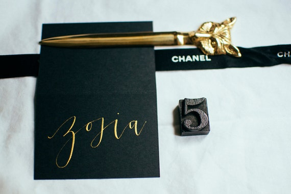 Black modern calligraphy place card with gold ink wedding
