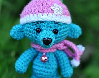 Cute Blue crochet teddy bear in a purple hat. Crochet bear toy.